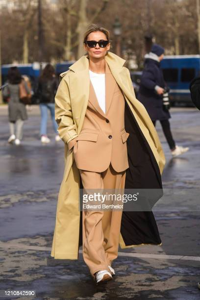 Guest wears sunglasses, a yellow trench coat, a brown jacket, flared pants, sneakers, a white t-shirt, outside Chanel, during Paris Fashion Week -...