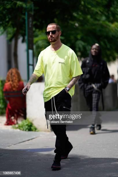 A guest wears sunglasses a yellow tshirt outside Rick Owens during Paris Fashion Week Menswear SpringSummer 2019 on June 21 2018 in Paris France