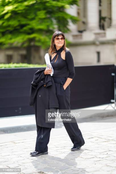 A guest wears sunglasses an black halter keyhole top flare pants black shoes earrings outside the Chanel Cruise Collection 2020 At Grand Palais on...