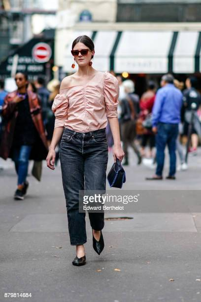 A guest wears sunglasses an offshoulder ruffle silk pink top black jeans outside Koche during Paris Fashion Week Womenswear Spring/Summer 2018 on...