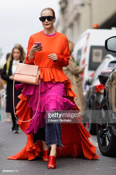 A guest wears sunglasses an orange and pink ruffle pleated dress cropped jeans red shoes a pink bag outside Giambattista Valli during Paris Fashion...