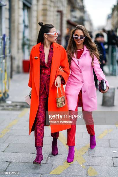 A guest wears sunglasses an orange coat a red flower print suit purple shoes a guest wears sunglasses a pink coat red pants purple shoes outside...