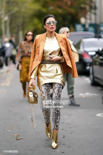 A guest wears sunglasses an orange jacket a golden shiny short dress snake pattern print leggings golden shiny pointy shoes a golden quilted bag...