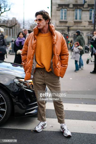 Guest wears sunglasses, an orange knit sweater, an orange leather puffer jacket, brown and yellow checkered pants with fringed hem, silver-tone and...