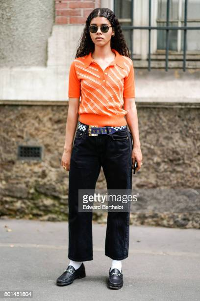 A guest wears sunglasses an orange polo shirt black pants white socks black shoes outside the Paul Smith show during Paris Fashion Week Menswear...