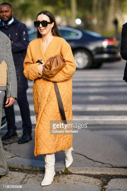 Guest wears sunglasses, an orange quilted coat, a brown leather puff bag, white pointy boots, outside Loewe, during Paris Fashion Week - Womenswear...