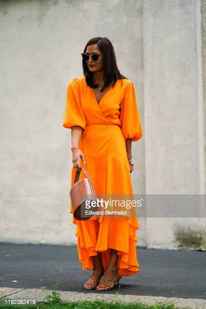 A guest wears sunglasses an orange ruffled dress a brown leather bag outside the Prada show during Milan Fashion Week Spring/Summer 2020 on September...