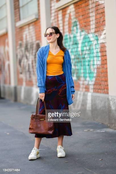 Guest wears sunglasses, an orange ruffled V-neck t-shirt, a blue long wool cardigan, black with burgundy / neon blue / orange print pattern long tube...