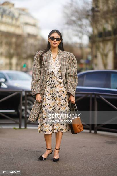 Guest wears sunglasses, an oversized long blazer with checked pattern, earrings, a brown leather bag, a dress with printed horses, black pointy...