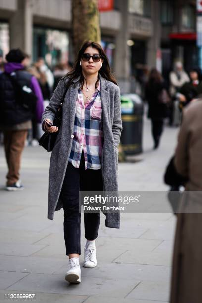 A guest wears sunglasses Apple Airpods a grey tweed coat a navy blue and pink checkered shirt black pants white sneakers during London Fashion Week...