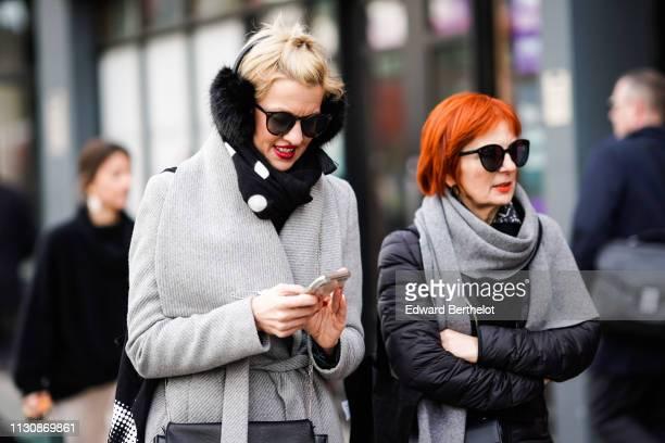 A guest wears sunglasses black fur earmuffs a grey scarf a guest wears sunglasses a large grey scarf a black padded jacket during London Fashion Week...