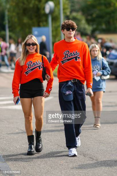 Guest wears sunglasses, black sunglasses, silver pendant earrings, a neon orange Boss sweater, black shorts, black shiny leather ankle boots, a guest...