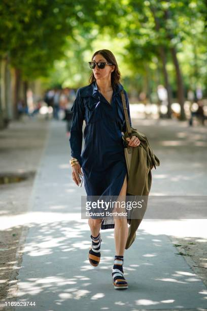 A guest wears sunglasses bracelets a navy blue shirtdress white and tancolor strappy sandals outside Berluti during Paris Fashion Week Menswear...
