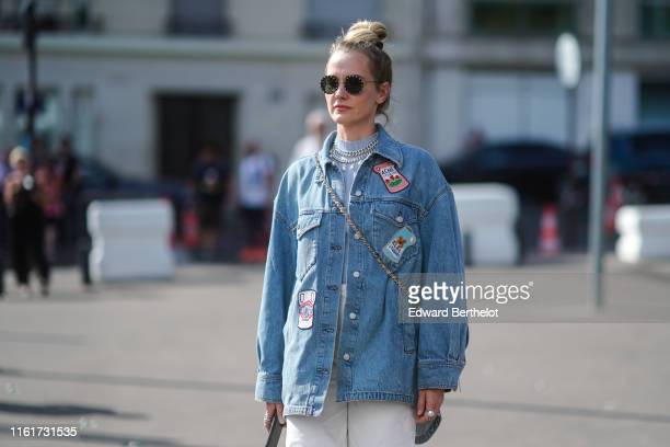 A guest wears sunglasses chain necklaces a blue denim Acne Studios ripped jacket with patches white pants outside Acne during Paris Fashion Week...
