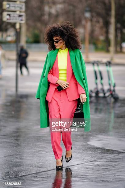 A guest wears sunglasses Chanel earrings green coat a neon pink pantsuit a neon yellow top openwork black pumps a bottle of perfume shaped brown...