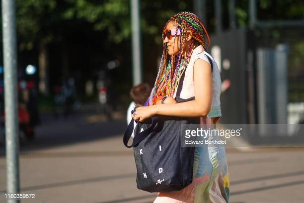 A guest wears sunglasses colorful braids a large black tote bag a colorful patchworked top a colorful patchworked skirt outside Acne during Paris...