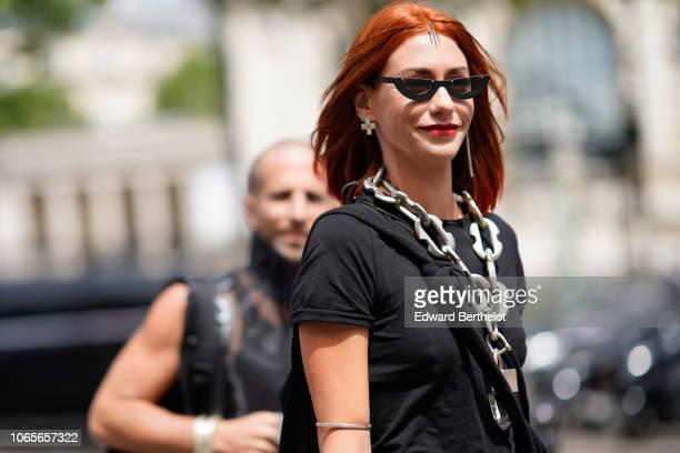 A guest wears sunglasses crossshaped earrings a chain necklace a black tshirt outside Rick Owens during Paris Fashion Week Menswear SpringSummer 2019...