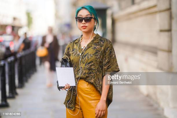 Guest wears sunglasses, earphones, a green khaki shirt with printed leaves, orange leather pants, outside Ralph & Russo, during Paris Fashion Week...