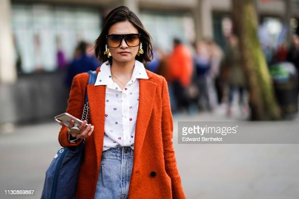 A guest wears sunglasses earphones a white shirt with multicolored dots high waist jeans an orange coat during London Fashion Week February 2019 on...