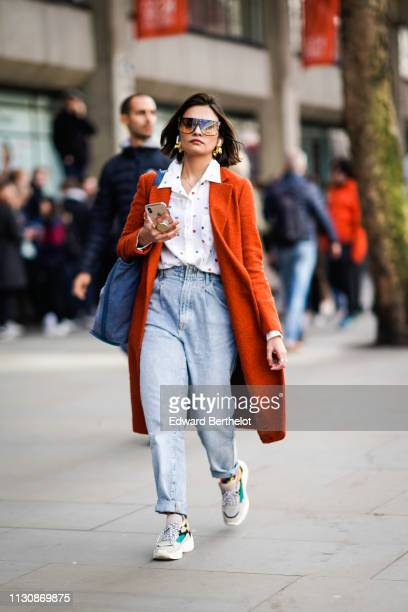 A guest wears sunglasses earphones a white shirt with multicolored dots high waist cuffed jeans an orange coat multicolored sneakers during London...