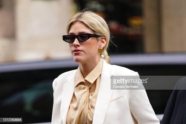Guest wears sunglasses, earrings, a beige gathered shirt, a white coat, outside Giambattista Valli, during Paris Fashion Week - Womenswear...
