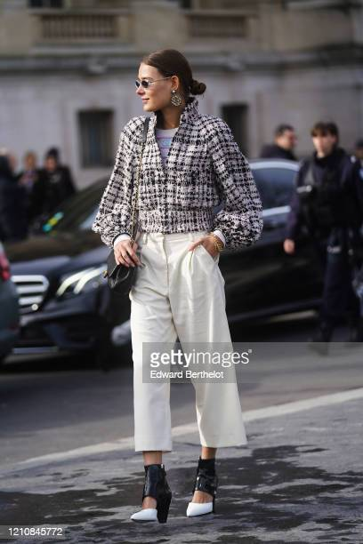Guest wears sunglasses, earrings, a black and white tweed jacket, white cropped flared pants, black and white shiny pointy shoes, a bag, outside...