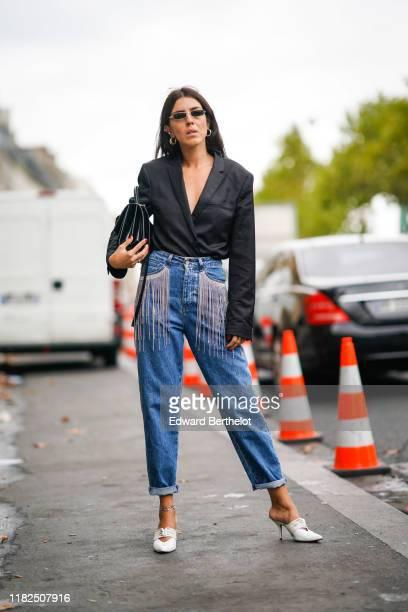 A guest wears sunglasses earrings a black bag a black shirt a black bag blue denim rolledup hem pants with pockets decorated with rhinestone fringes...