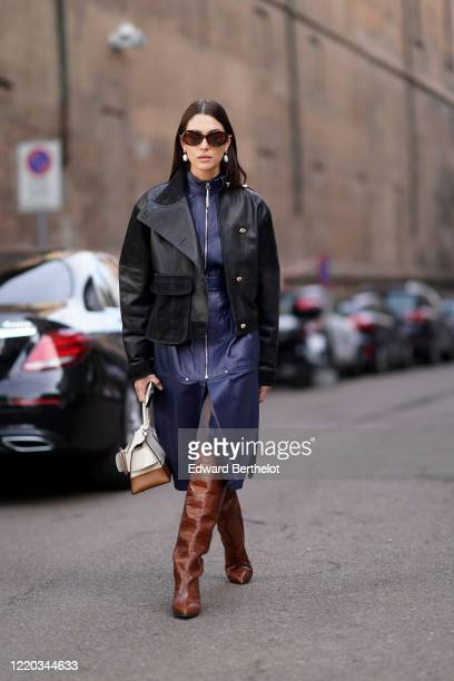 Guest wears sunglasses, earrings, a black leather jacket, a blue leather long dress with a front zipper, brown leather crocodile pattern pointy high...