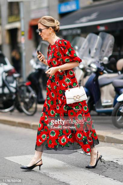 A guest wears sunglasses earrings a black muslin dress with large red and green flowers print and puff sleeves a white Dolce Gabbana bag black...