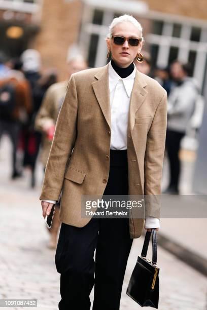 Guest wears sunglasses, earrings, a blazer jacket, a bag, a white shirt, black pants, during London Fashion Week Men's January 2019 on January 06,...