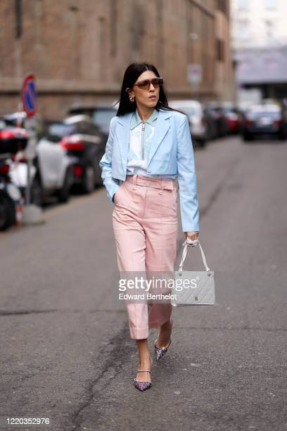Guest wears sunglasses, earrings, a blue jacket, a polo shirt with a front zipper, pink cropped pants, purple pointy shoes, outside Sportmax, during...