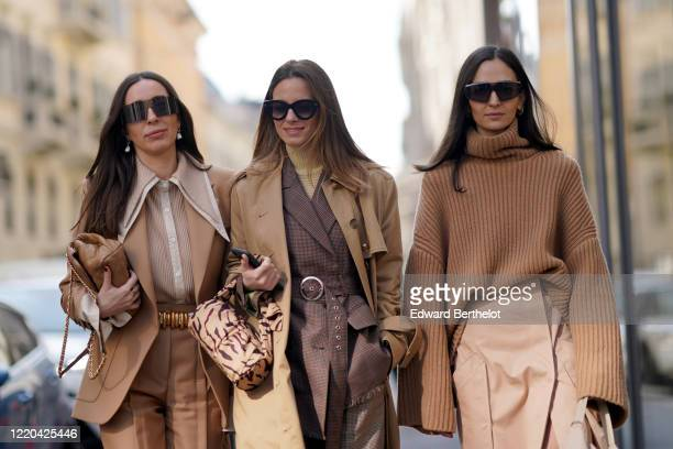 Guest wears sunglasses, earrings, a brown jacket, a brown shirt, a belt, pants ; a guest wears a brown trench long coat, a gray jacket ; a guest...