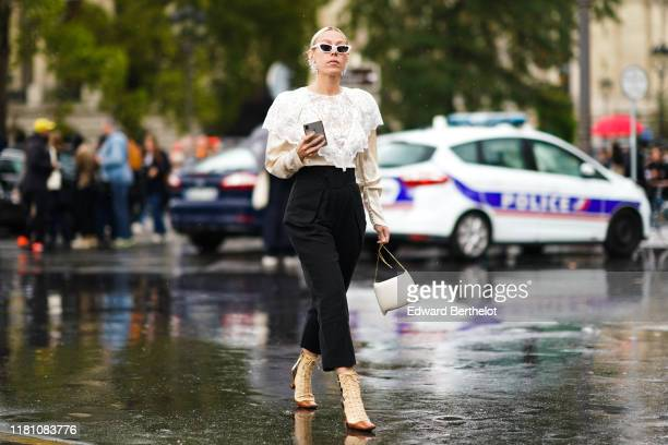 Guest wears sunglasses, earrings, a cream-color blouse with a white lace bertha collar, black pants, a white bag, camel and tan-color heeled...