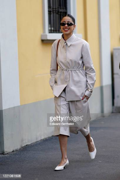 Guest wears sunglasses, earrings, a gray jacket, shorts, white shoes outside Tod's, during Milan Fashion Week Fall/Winter 2020-2021 on February 21,...