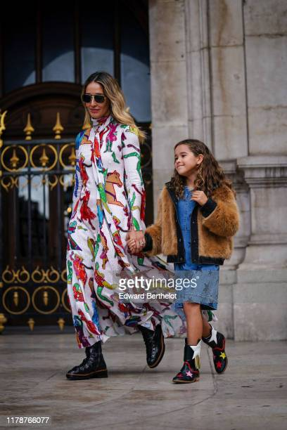 A guest wears sunglasses earrings a hineck long sleeves flowing long dress with colorful patterns and a lavaliere a lustrous salmoncolor velvet...
