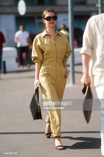 A guest wears sunglasses earrings a light mustardyellow jumpsuit a black handbag black strappy sandals outside Acne during Paris Fashion Week Haute...