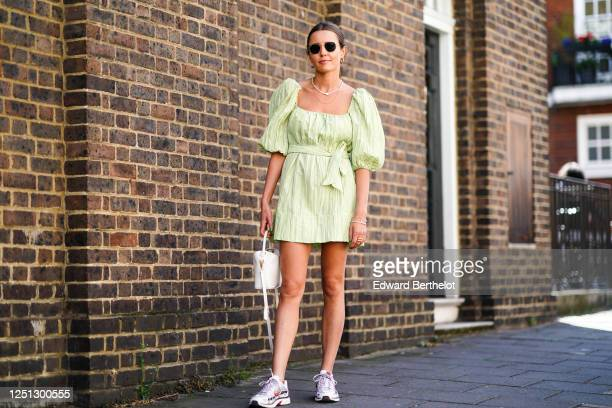 Guest wears sunglasses, earrings, a necklace, a green gathered dress with puff sleeves/shoulders and low-neck, Nike sneakers shoes, a white bag,...