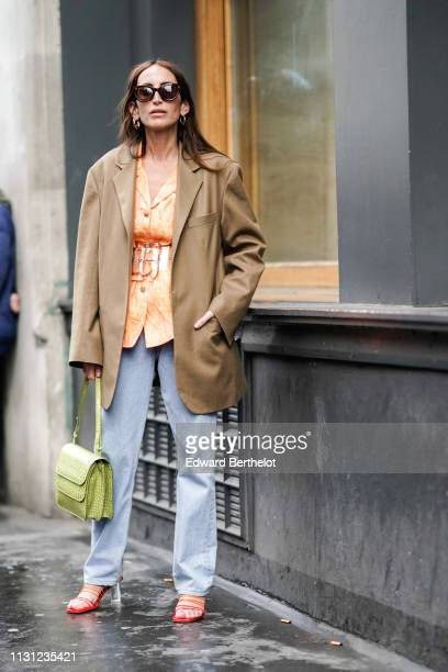 A guest wears sunglasses earrings a peach color shirt a translucent vinyl belt a camel jacket jeans a green doubleflap handbag red and orange sandals...