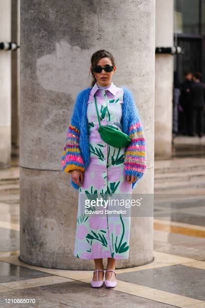 Guest wears sunglasses, earrings, a pink and green floral print shirt-dress, a green bag, light pink square end T-strap shoes, a blue knit fluffy...