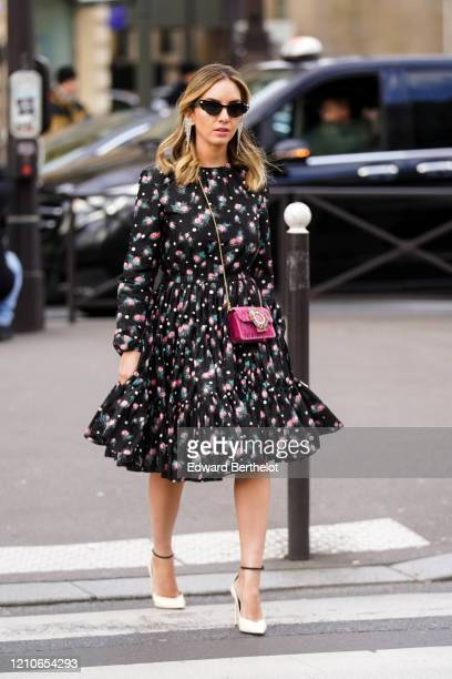 Guest wears sunglasses, earrings, a pleated dress with printed flowers, a purple bag, white pointy shoes, outside Miu Miu, during Paris Fashion Week...