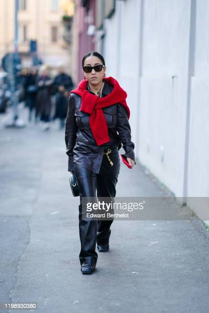 A guest wears sunglasses earrings a red pullover a black leather jacket black leather flared pants outside Marni during Milan Fashion Week...