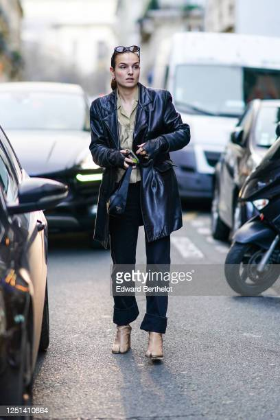 Guest wears sunglasses, earrings, a sage-green shirt, a black leather short coat, a navy-blue Prada bag, navy-blue jeans with turned-up hems, beige...