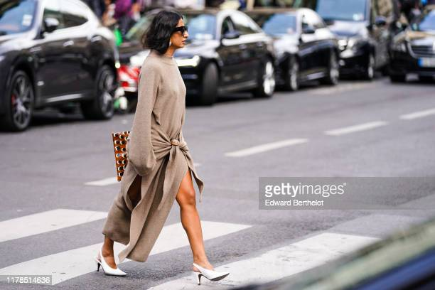 Guest wears sunglasses, earrings, a sand-color long sleeves knit dress slit on the sides, white pointy slingback heels, outside Giambattista Valli,...