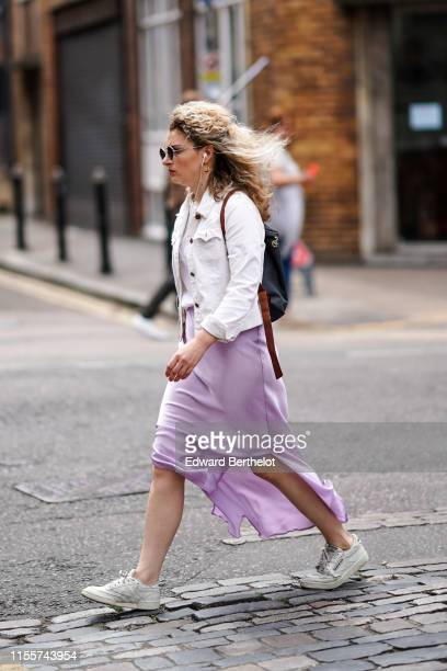 A guest wears sunglasses earrings a white corduroy jacket a black backpack a mauve lustrous flowing skirt white Reebok sneakers during London Fashion...