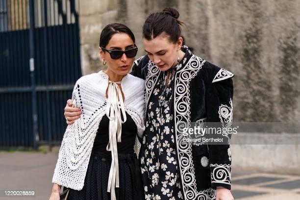 Guest wears sunglasses, earrings, a white crochet short cape, a black top, a black pleated skirt, white pants, a Loewe bag ; A guest wears earrings,...