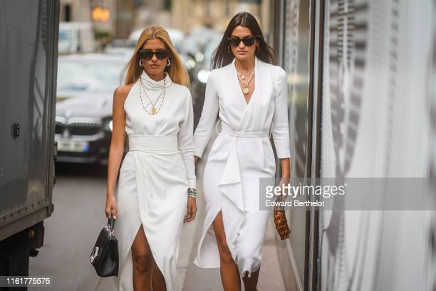 Guest wears sunglasses, earrings, a white dress, a necklace, outside Ralph & Russo, during Paris Fashion Week -Haute Couture Fall/Winter 2019/2020,...