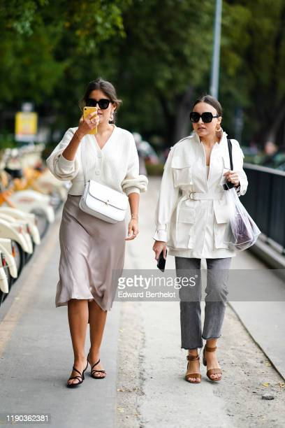 Guest wears sunglasses, earrings, a white knit top, a white crossbody bag, a light grey skirt, black suede strappy heeled sandals ; A guest wears...