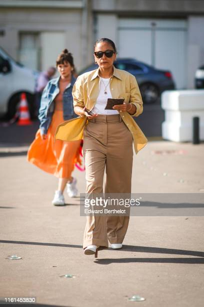 Guest wears sunglasses, earrings, a white top, a sand-color shirt, camel wide-legs cuffed pants, white heeled pumps, outside Acne, during Paris...