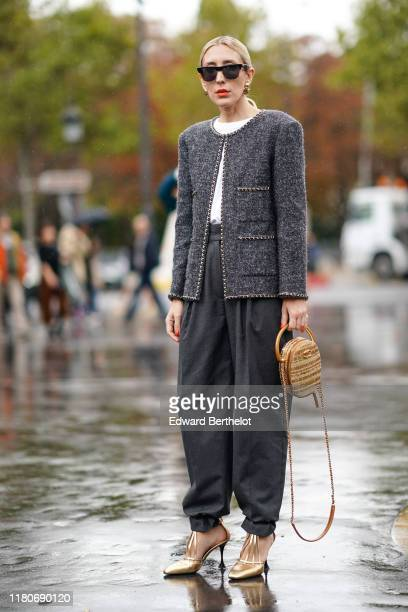 A guest wears sunglasses earrings a wite top a gray tweed jacket gray pants a brown bag golden shoes outside Chanel during Paris Fashion Week...