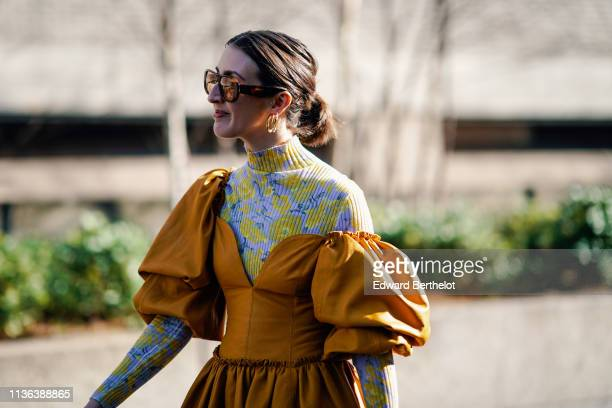 A guest wears sunglasses earrings a yellow and purple floral print turtleneck an orange ruffled gathered dress with puff sleeves during London...